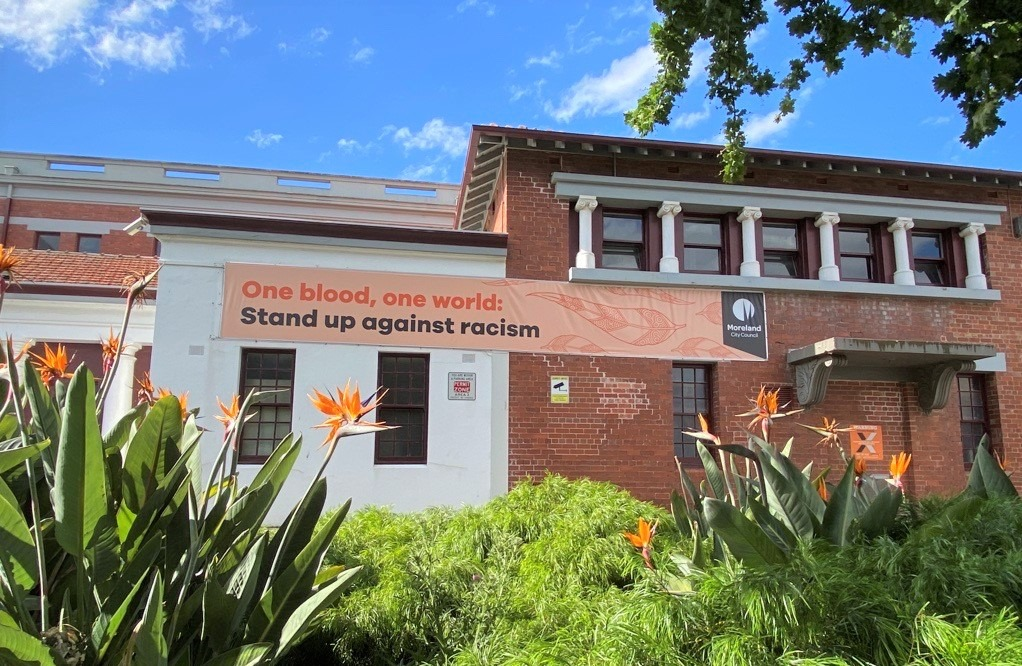 Banner outside of Coburg Town Hall with text 'one blood, one world: stand up against racism'