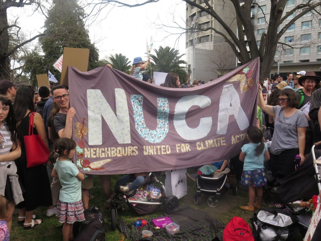 A group of people including kids holding a banner with the word NUCA stitched into it
