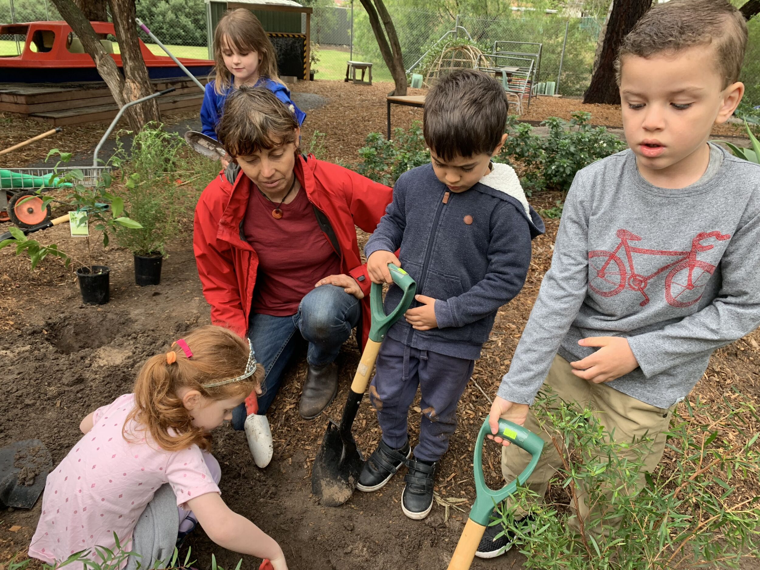 Four preschool aged children with shovels digging holes for native trees with help from an adult instructor