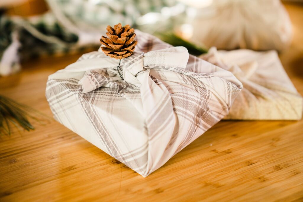 Present wrapped in a cloth with a small pine cone attached