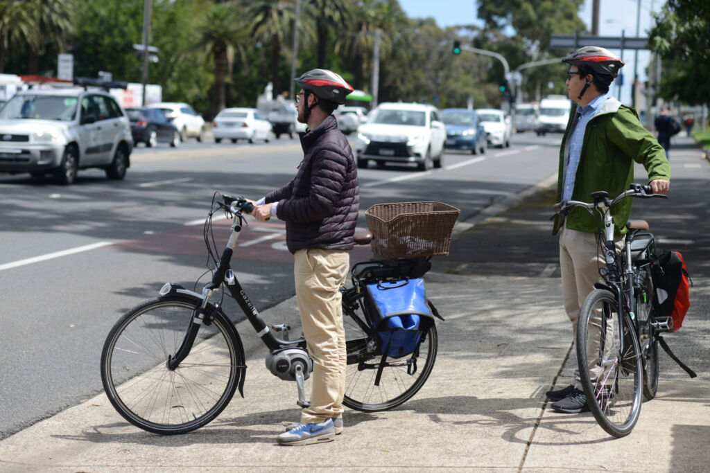 Two male adults with electric bikes waiting to cross a traffic filled road