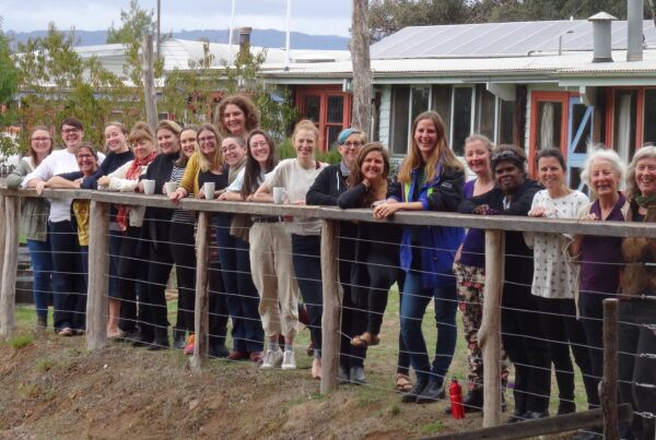 Approximately 20 women of different ages leaning against a fence with a house with solar panels in the background