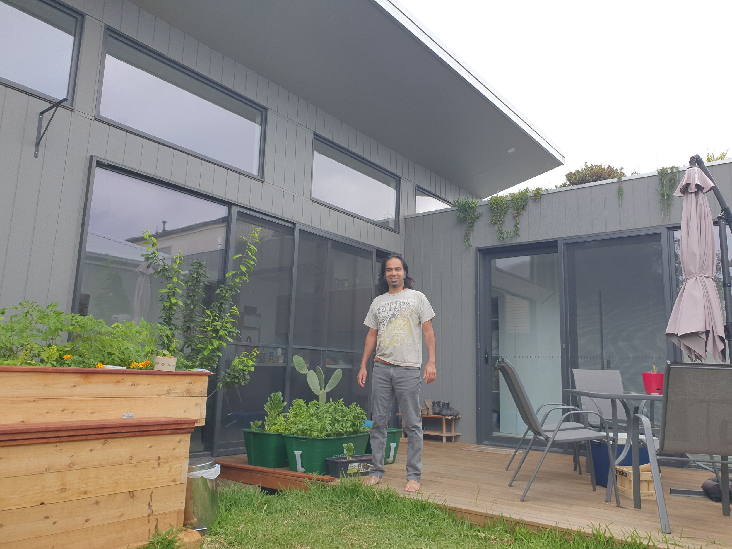 Photo of a man on a back deck of a sustainable house with raised vegetable boxes